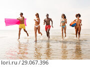 Купить «friends run with beach ball and swimming mattress», фото № 29067396, снято 29 июля 2018 г. (c) Syda Productions / Фотобанк Лори