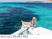 Купить «Woman relaxing on a summer sailing cruise, sitting on a luxury catamaran near picture perfect white sandy beach on Spargi island in Maddalena Archipelago, Sardinia, Italy.», фото № 29067432, снято 18 августа 2019 г. (c) Matej Kastelic / Фотобанк Лори