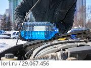 Купить «Man filling a windshield washer tank of a car by antifreeze on winter Moscow street», фото № 29067456, снято 18 марта 2018 г. (c) Георгий Дзюра / Фотобанк Лори
