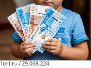 Купить «Маленький мальчик держит в руках бумажные деньги», фото № 29068224, снято 10 сентября 2018 г. (c) Игорь Низов / Фотобанк Лори