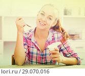 Купить «portrait of young woman eating yoghurt at kitchen», фото № 29070016, снято 11 июля 2020 г. (c) Яков Филимонов / Фотобанк Лори