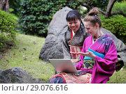 Купить «Две девушки в японском кимоно смотрят в ноутбук и смеются», фото № 29076616, снято 27 марта 2011 г. (c) Александр Гаценко / Фотобанк Лори