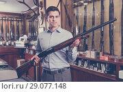 Купить «Handsome adult male in hunting shop with rifle in hands», фото № 29077148, снято 11 декабря 2017 г. (c) Яков Филимонов / Фотобанк Лори