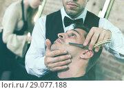 Male getting shave with straight razor in salon. Стоковое фото, фотограф Яков Филимонов / Фотобанк Лори