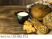 Купить «Food. Country breakfast. Assortment of fresh bread baked in a bakery, biscuits and a mug with milk on a wooden table background», фото № 29082512, снято 25 августа 2018 г. (c) Светлана Евграфова / Фотобанк Лори