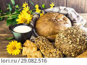Купить «Food. Rustic still life. Assortment of fresh bread baked in a bakery, biscuits and a mug with milk on a wooden table background», фото № 29082516, снято 25 августа 2018 г. (c) Светлана Евграфова / Фотобанк Лори