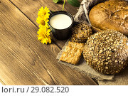 Купить «Food. Rustic still life. Assortment of fresh baked bread in the bakery, biscuits and mug with milk on the background of the texture of the wooden table», фото № 29082520, снято 25 августа 2018 г. (c) Светлана Евграфова / Фотобанк Лори