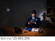 Купить «Detective sitting in dark room in vintage concept», фото № 29083256, снято 13 июля 2017 г. (c) Elnur / Фотобанк Лори