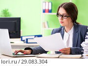 Купить «Young female employee very busy with ongoing paperwork», фото № 29083304, снято 8 июня 2018 г. (c) Elnur / Фотобанк Лори