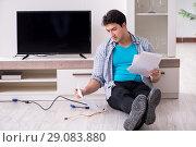 Купить «Man trying to fix broken tv», фото № 29083880, снято 9 марта 2018 г. (c) Elnur / Фотобанк Лори