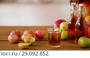 Купить «glass and bottles of apple juice on wooden table», видеоролик № 29092852, снято 7 сентября 2018 г. (c) Syda Productions / Фотобанк Лори