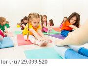 Купить «Diligent girl doing stretching exercise on mat», фото № 29099520, снято 15 апреля 2017 г. (c) Сергей Новиков / Фотобанк Лори