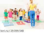 Купить «Group of happy kids jumping ropes at gym lesson», фото № 29099548, снято 15 апреля 2017 г. (c) Сергей Новиков / Фотобанк Лори