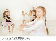 Купить «Little girls doing exercises in light ballet class», фото № 29099576, снято 15 апреля 2017 г. (c) Сергей Новиков / Фотобанк Лори