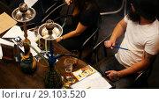 Купить «Group of young people enjoying spending time in the restaurant, drinking cocktails and smoking hookah, top view», видеоролик № 29103520, снято 21 сентября 2018 г. (c) Константин Шишкин / Фотобанк Лори