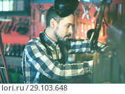Купить «Male worker working on leather for belt in leather», фото № 29103648, снято 20 октября 2018 г. (c) Яков Филимонов / Фотобанк Лори