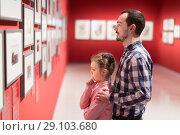Купить «Young father and girl exploring exhibition», фото № 29103680, снято 20 сентября 2018 г. (c) Яков Филимонов / Фотобанк Лори