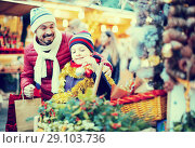 Купить «Happy man with small daughter buying decorations», фото № 29103736, снято 20 сентября 2018 г. (c) Яков Филимонов / Фотобанк Лори