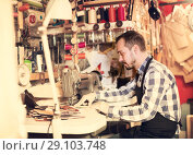 Купить «Male worker stitching new belt», фото № 29103748, снято 19 октября 2018 г. (c) Яков Филимонов / Фотобанк Лори