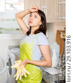 Купить «Tired girl housewife in apron holding gloves at kitchen», фото № 29103916, снято 18 апреля 2018 г. (c) Яков Филимонов / Фотобанк Лори
