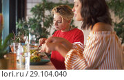 Купить «female friends eating at restaurant», видеоролик № 29104040, снято 23 августа 2018 г. (c) Syda Productions / Фотобанк Лори
