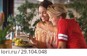 Купить «female friends with smartphone at restaurant», видеоролик № 29104048, снято 23 августа 2018 г. (c) Syda Productions / Фотобанк Лори