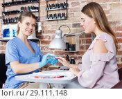 Купить «Manicurist woman in gloves doing manicure to female client in salon», фото № 29111148, снято 30 мая 2018 г. (c) Яков Филимонов / Фотобанк Лори