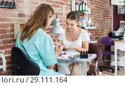 Купить «Woman who doing manilure sitting in nail salon», фото № 29111164, снято 30 мая 2018 г. (c) Яков Филимонов / Фотобанк Лори
