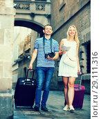 Купить «Cheerful traveling man and girl walking in city», фото № 29111316, снято 16 декабря 2018 г. (c) Яков Филимонов / Фотобанк Лори