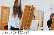 Young attractive woman standing behind the easel close up. Стоковое видео, видеограф Константин Шишкин / Фотобанк Лори