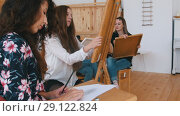 Attractive girls are sitting behind the easel close up. Стоковое видео, видеограф Константин Шишкин / Фотобанк Лори