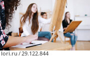 Attractive girls are sitting behind the easel close up hands. Стоковое видео, видеограф Константин Шишкин / Фотобанк Лори