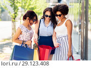 Купить «happy women showing shopping bags in city», фото № 29123408, снято 22 июля 2018 г. (c) Syda Productions / Фотобанк Лори