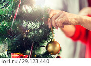 Купить «close up of senior woman decorating christmas tree», фото № 29123440, снято 14 сентября 2017 г. (c) Syda Productions / Фотобанк Лори