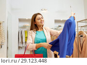 Купить «happy woman choosing clothes at clothing store», фото № 29123448, снято 19 февраля 2016 г. (c) Syda Productions / Фотобанк Лори