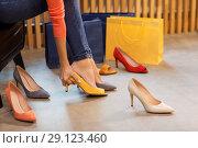 Купить «young woman trying high-heeled shoes at store», фото № 29123460, снято 22 сентября 2017 г. (c) Syda Productions / Фотобанк Лори