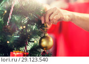 Купить «close up of senior woman decorating christmas tree», фото № 29123540, снято 14 сентября 2017 г. (c) Syda Productions / Фотобанк Лори