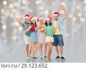 Купить «happy friends in santa hats over festive lights», фото № 29123652, снято 30 июня 2018 г. (c) Syda Productions / Фотобанк Лори