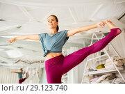 Купить «woman doing yoga hand-to-big-toe pose at studio», фото № 29123740, снято 21 июня 2018 г. (c) Syda Productions / Фотобанк Лори