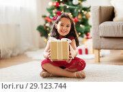 Купить «happy girl with christmas gift at home», фото № 29123744, снято 29 августа 2018 г. (c) Syda Productions / Фотобанк Лори