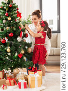 Купить «happy family decorating christmas tree at home», фото № 29123760, снято 29 августа 2018 г. (c) Syda Productions / Фотобанк Лори