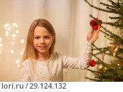 Купить «happy girl in red dress decorating christmas tree», фото № 29124132, снято 22 декабря 2017 г. (c) Syda Productions / Фотобанк Лори