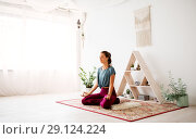 Купить «woman meditating in lotus pose at yoga studio», фото № 29124224, снято 21 июня 2018 г. (c) Syda Productions / Фотобанк Лори