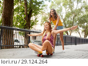 Купить «teenage girls riding skateboard on city street», фото № 29124264, снято 19 июля 2018 г. (c) Syda Productions / Фотобанк Лори