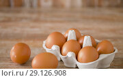Купить «close up of eggs in cardboard box on wooden table», видеоролик № 29126908, снято 21 августа 2018 г. (c) Syda Productions / Фотобанк Лори