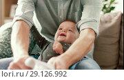 Купить «father putting sock on baby daughters foot», видеоролик № 29126992, снято 17 сентября 2018 г. (c) Syda Productions / Фотобанк Лори