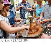Купить «Sochi, Russia - June 1. 2018. people gain mineral water from Narzan source Chvizhepse», фото № 29127304, снято 1 июня 2018 г. (c) Володина Ольга / Фотобанк Лори
