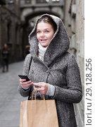 Купить «young female with mobile in hood», фото № 29128256, снято 11 ноября 2017 г. (c) Яков Филимонов / Фотобанк Лори