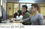 Купить «A group of Asian and European students use computers in the classroom», видеоролик № 29131820, снято 24 сентября 2018 г. (c) Поцелуев Константин Валерьевич / Фотобанк Лори