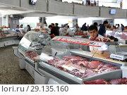 Купить «Tashkent, Uzbekistan - May 01, 2017: Unknown meat seller sits idle at meat pavilion in Chorsu market.», фото № 29135160, снято 1 мая 2017 г. (c) age Fotostock / Фотобанк Лори